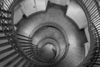 Blick von oben in ein Treppenhaus. Duchmesser ca. 10 Meter, das ganze Treppenhaus ist rund und v.a. das Treppengeländer läuft als Spirale vom Betrachter weg. Höhe 4-5 Stockwerke