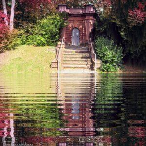 Ein gemauertes Portal aus rotem Standstein, hinauf führen 7 Treppenstufen. Um das Portal herum ein grüner und viele rotblättrige Büsche und Bäume. Auf der Ebene, wo der Fotograf steht ist das Bild bearbeitet, statt des Originalgrundes wurde eine Spiegelung des oberen Teils eingefügt, also von Treppe, Portal und Bäumen, wie in einem Weiher.