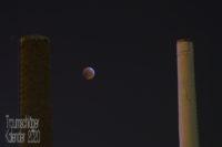 """Nachtfoto: Zwei Schornsteine eines Heizkraftwerks, vom städtichen Lichtkonzept leicht angestrahlt. Zwischen den Schornsteinen nicht ganz mittig ein Vollmond in dunkelroter Färbung, vom Blutmond oder ener (partiellen) Mondfinsternis. Einige Betrachter sagten spontan: """"Mond-Pong!"""""""