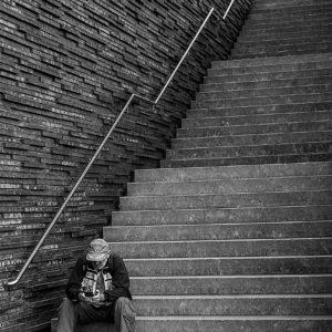 Schwarzweiß-Foto. Auf den untersten drei Stufen einer langen, in drei Abschnitte gegliederten Treppe, sitzt ein Mann, mit Baseballcap und Fanschal, er schaut auf sein Handy. Den Rest des Bildes dominiert die Treppe und die sie begrenzende Wand, die aus rauhen Steinen grob zusammengesetzt ist, mit viel Struktur.