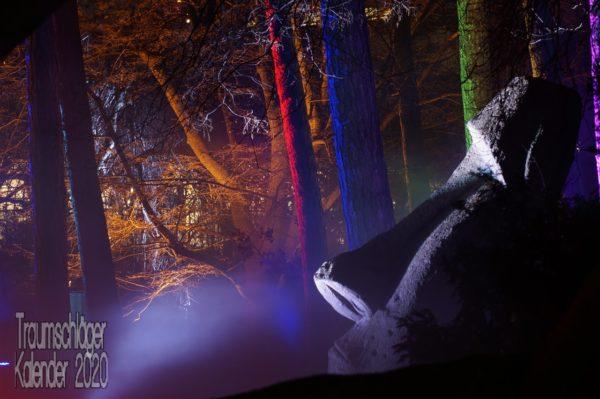 Nachtbild mit bunter Beleuchtung. In rotem, blauen, grünen, orangegelben und violettem Licht Bäume und im Vordergrund heller angestrahlt vermutlich eine Skulptur.