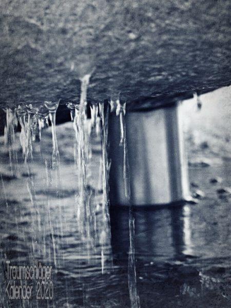 Detailfoto eines Brunnens. Im Hintergrund ein Wasserrohr, im Vordergrund herunterlaufendes und heruntertropfendes Wasser, das von der Unterseite eines abgerundeten Steins heruntertropft.