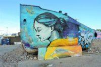 Dokumentarisches Foto: Graffito einer jungen Frau in Türkistönen, die Haare zum Pferdeschwanz gebunden und mit geschlossenen Augen leicht lächelnd, Malgrund für das Graffito ist ein auf Land gelegtes Schiff, vermutlich ein Fluss-Lastkahn. Graffitto von Hanasaari Hanaholmen in Helsinki, Finnland