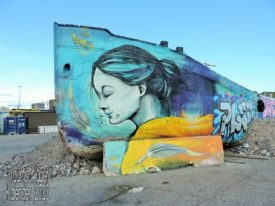 Dokumentarisches Foto: Graffito einer jungen Frau in Türkistönen, die Haare zum Pferdeschwanz gebunden und mit geschlossenen Augen leicht lächelnd, Malgrund für das Graffito ist ein auf Land gelegtes Schiff, vermutlich ein Fluss-Lastkahn.