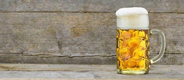 Ein mit hellgelbem Bier gefüllter Maßkrug. Der Schaum fält ganz leicht über den Rand des Glases, rinnt aber nicht herunter. Tisch und Hintergrund sind altes, vom Wetter patiniertes grau gewordenes Holz. Sonst nichts.