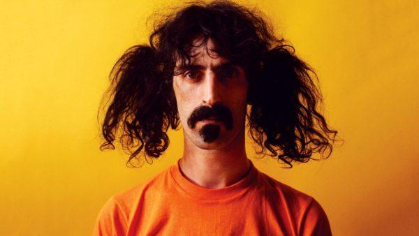 """Frank Zappa. vor gelbem Hintergrund, mit orangenem T-Shirt (vor gelb fast unsichtbar).Mit Schnurrbart, Goatee und links und rechts je einem zerzausten """"Pferdeschwanz"""" (im Gegensatz zum geflochtenen Zopf)"""