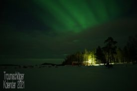 Winterlandschaft im Dunkeln. Am Rand eines Wäldchens steht ein Haus, wirkt wie das typische schwedische rote Holzhaus. Im Vordergrund verschneite Ebene und über dem Haus leuchtet grün das Nordlicht