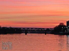 In kräftigem Abendrot und Gegenlicht eine Metallfachwerkbrücke über einen Fluß. Durchs Gegenlicht alles nur als Silihoutte zu sehen, an den Seiten des BIldes ist noch die Uferbewachsung zu erkennen