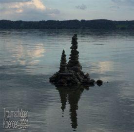 im Uferbereich eines Sees hat jemand Steine aufgetürmt. Stück für Stück aufeinander gesetzt und ausbalanciert ist eine Skulptur entstanden, ca 1m hoch und mit zwei hohen, schlanken Türmen. Im Bildhintergrund ist das andere Ufer zu sehen